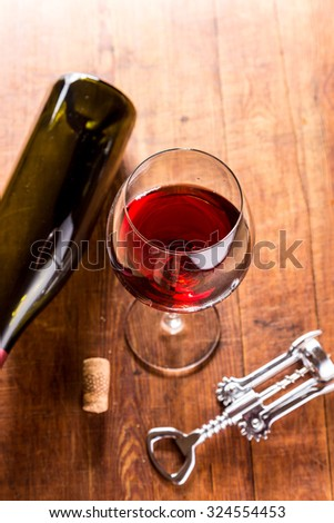 Pouring red wine glass against wooden background - stock photo