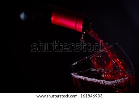 pouring red wine glass on dark light with space for text - stock photo
