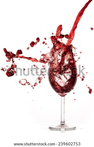 pouring red wine in goblet, isolated on white - stock photo