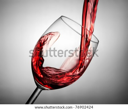 Pouring red wine in the glass - stock photo