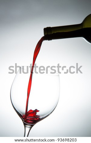 Pouring red wine into a glass. - stock photo