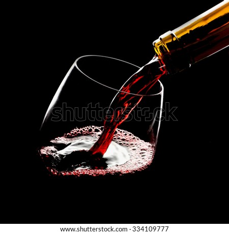 Pouring red wine into the glass against black background - stock photo
