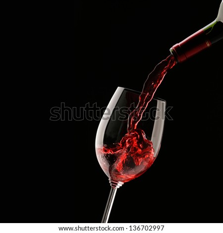 Pouring red wine into wine glass on a black background - stock photo
