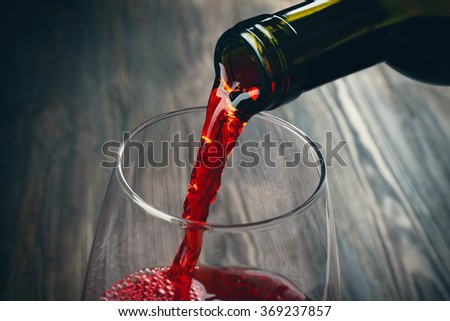 Pouring red wine on wooden background - stock photo