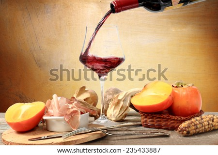 pouring red wine with table laden with persimmon, cob, decorative pumpkin and Parma ham against white background - stock photo