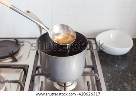 pouring soup into a pot on gas stove - stock photo