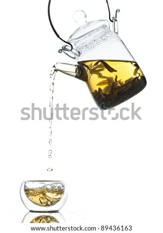 Pouring tea from glass pot into mug on white background - stock photo