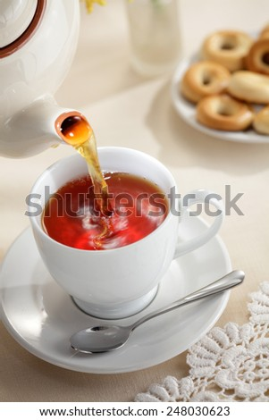 Pouring tea from teapot to the tea cup - stock photo