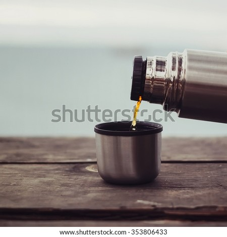 Pouring tea to cup from thermos on wooden table on background of sea. Theme tourism and travel. No people - stock photo