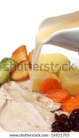 Pouring the gravy on to a plate of Christmas dinner - stock photo