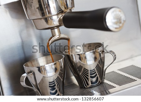 Pouring two cups of espresso with a domestic, stainless steel espresso machine. Shallow depth of field, with focus on the pouring spout. - stock photo