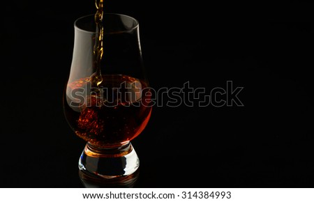 Pouring up a glass of whisky isolated over black background - stock photo
