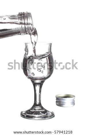 pouring vodka from a bottle into a glass - stock photo