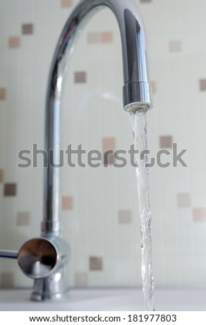 Pouring water from a tap in a bathroom - stock photo