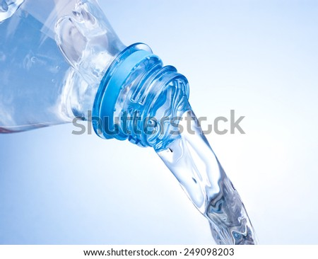 Pouring water from plastic bottle on blue background - stock photo