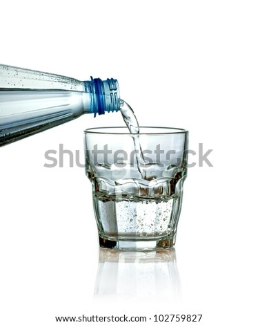 Pouring water from plastic bottle to glass isolated on white background - stock photo