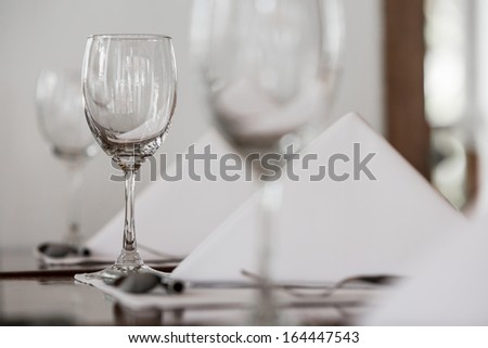 pouring water in glass with utensil on lunch table - stock photo