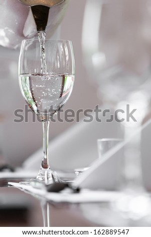 pouring water in glass with utensil on lunch table, selective focus with blurry forground - stock photo