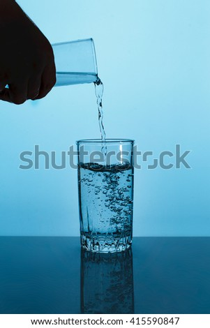 Pouring water into a glass against the blue background - stock photo