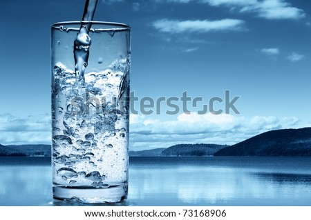 Pouring water into a glass against the nature background - stock photo