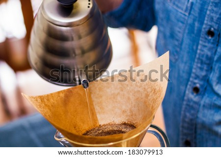 pouring water over coffee grounds - stock photo