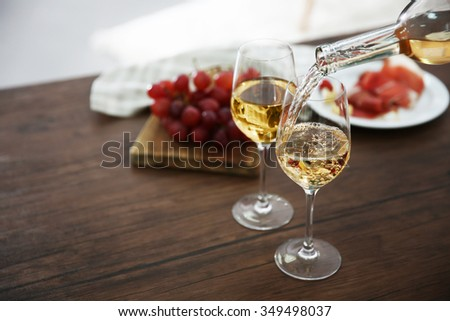 Pouring white wine from bottle into the wineglass on the table - stock photo