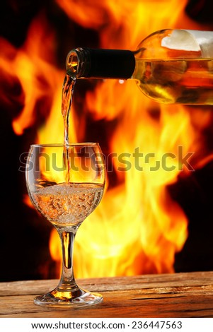 pouring wine in front of the fireplace - stock photo