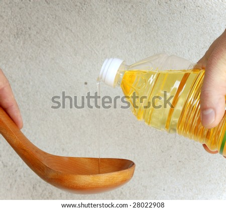 pouring yellow vegetable oil into wooden spoon over gray background - stock photo