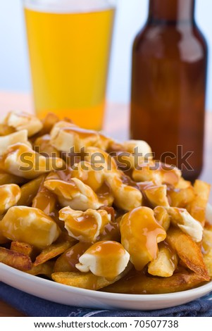 Poutine meal made with french fries, cheese curds and gravy. Beer in the background. Shallow depth of field. - stock photo