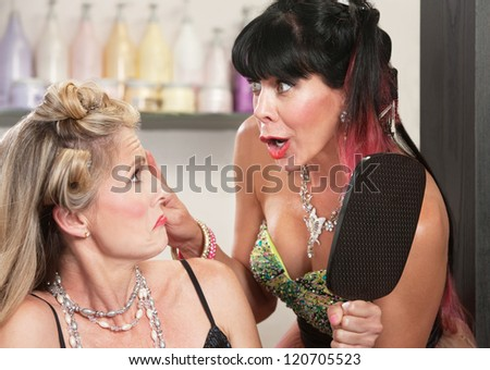 Pouting blond woman shown her bad hairdo by friend - stock photo