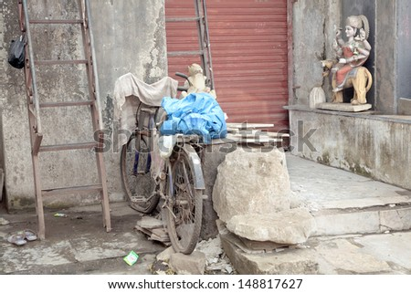 Poverty in indian village, religious statue in the corner - stock photo