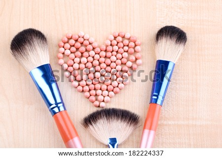 Powder balls and brushes on wooden background - stock photo
