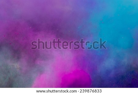 powder in different colours thrown into the air forming a huge cloud of smoke with little bits  - stock photo