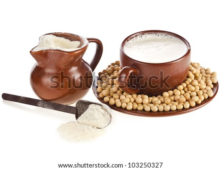powdered milk drink in clay pitcher , soy beans and cup on white background - stock photo