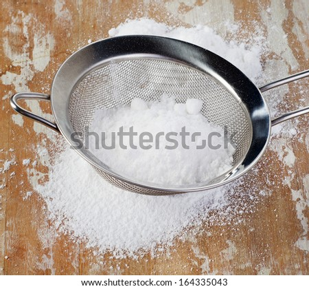 Powdered sugar in a metal sieve on wooden table. Selective focus - stock photo