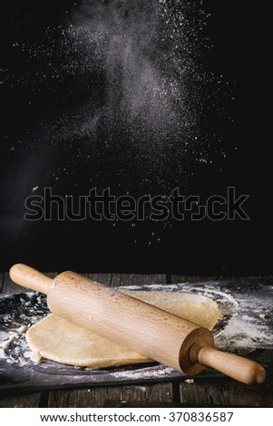 Powdering by flour rolled out dough for pasta with wooden rolling pin over wooden kitchen table. Dark rustic style. - stock photo