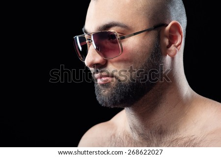 Power and confidence. Close up portrait of strong latino man with beard in sunglasses against black background. - stock photo