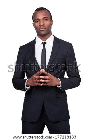 Power and success. Thoughtful young African man in formalwear holding hands clasped while standing isolated on white background  - stock photo