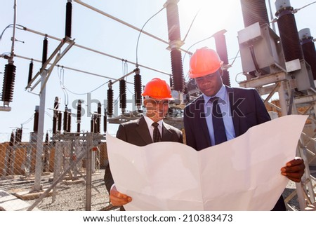 power company managers discussing blueprint at electrical substation  - stock photo