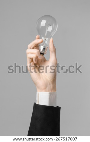 Power consumption and new business idea theme: man's hand in a black suit holding a light bulb on a gray background in studio - stock photo