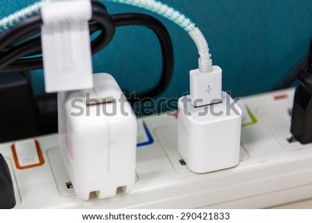 Power cord with several adapters and chargers for various electronic devices in a paperless office - stock photo