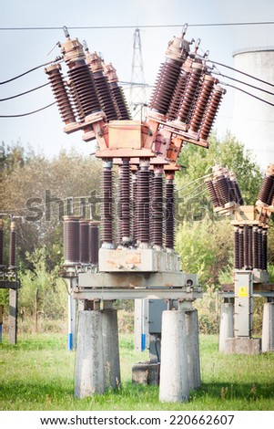 power distribution field with power station in background - stock photo