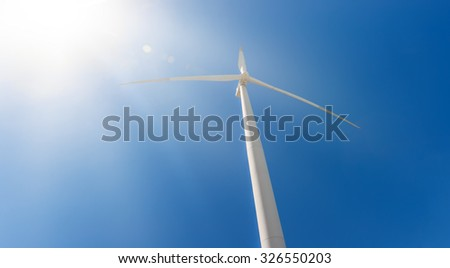 Power generating wind turbine on blue sky with bright sun rays - stock photo