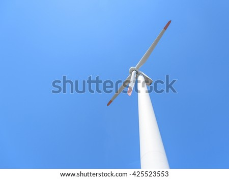 Power generation wind turbines against the blue sky with clouds. - stock photo