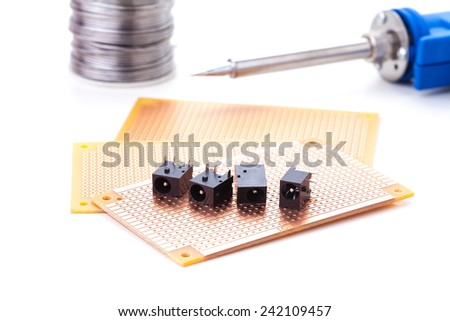 power jack female placed on the pcb. Electronic printed board. Soldering iron is background - stock photo