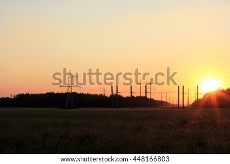 power line running over the horizon at sunset in the summer / electric and solar energy in the natural landscape - stock photo