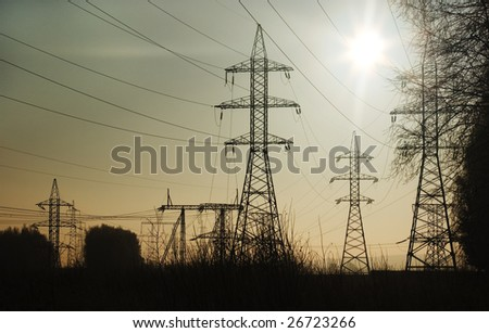 Power line silhouettes against sun light - stock photo
