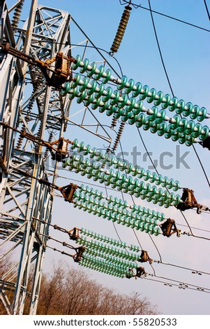 Power line wiring and insulators system over blue sky - stock photo