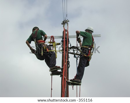 Power lineman working on a pole - stock photo