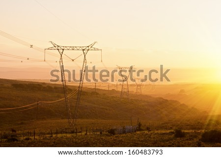 power lines and pylons receding into the distant sunny horizon - stock photo